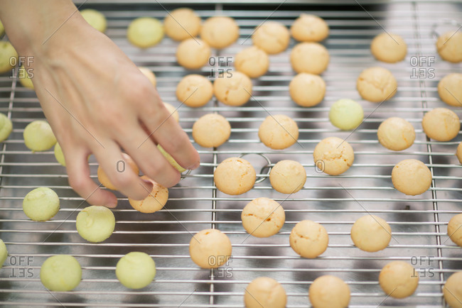 Hand placing macaroons on cooling rack