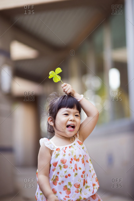 Little girl with fresh leaves on a playground