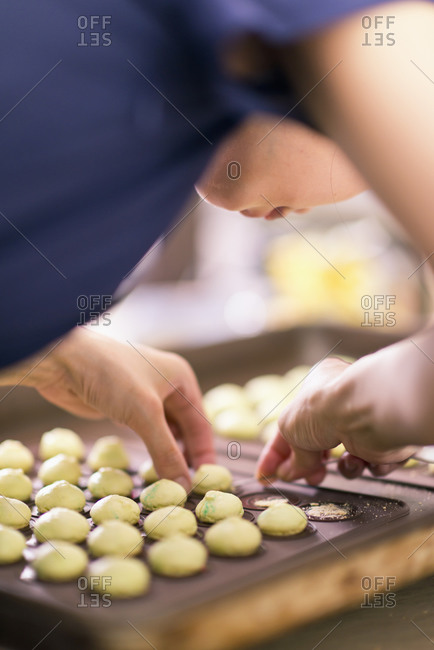 Young woman making macaroon dessert