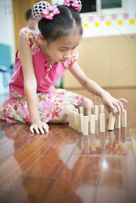 Child playing with wooden blocks on floor