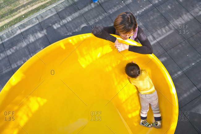 Child playing slid and mother looking at him