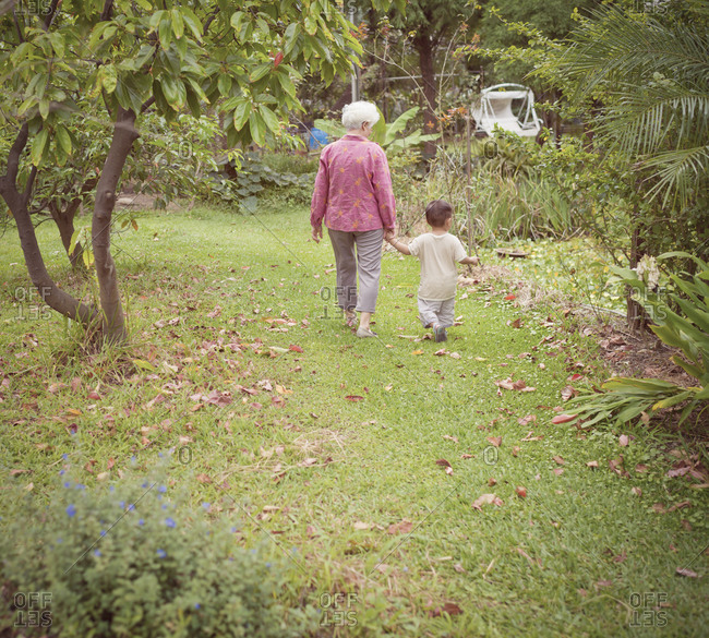 Grandmother with grandchild walking in a garden