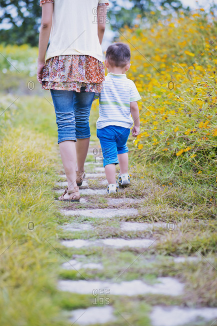 Mother and child walking on footpath in the garden