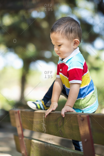 Child try to climb over a park bench