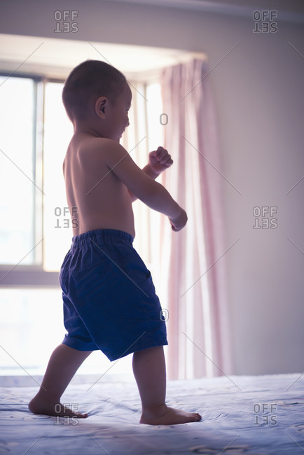 Boy playing on a bed
