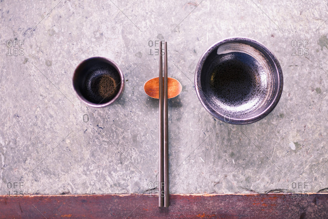 Chinese bowl, tea cup and chopsticks on old stone table