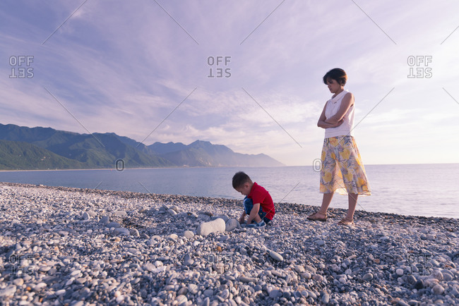 Young mother and kid playing on the beach at sunrise, Chihsingtan Beach, Hualian, Taiwan, Asia.