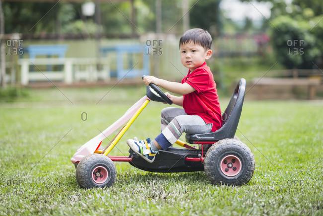 Little boy driving toy car in the garden