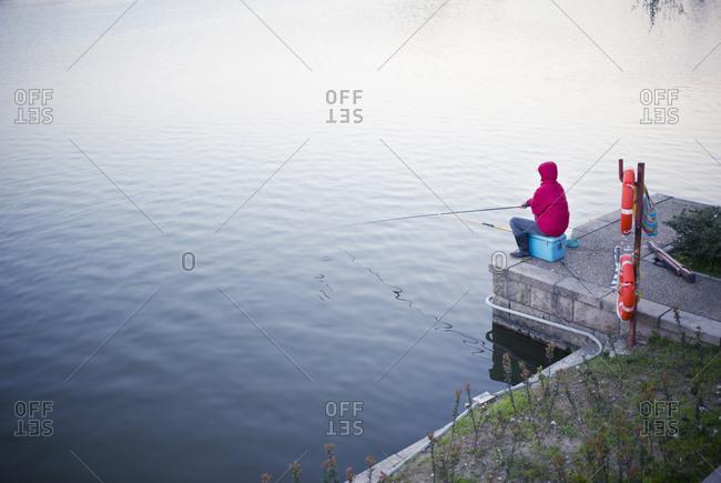 Man fishing on lake alone.