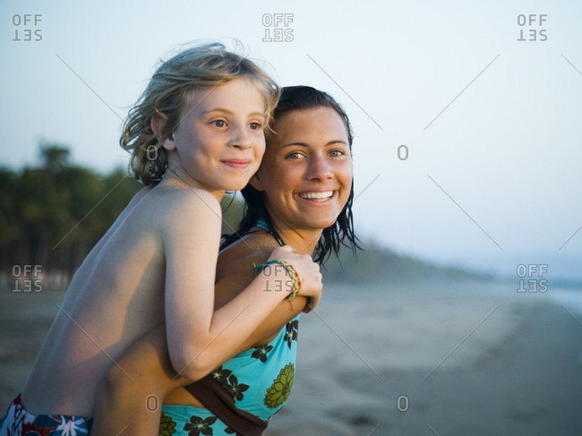 Young woman and little brother on beach
