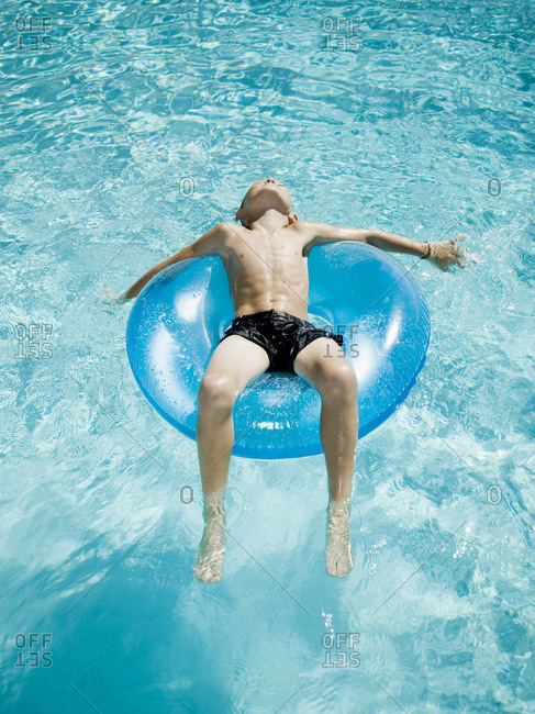 Young boy floating on life ring in swimming pool