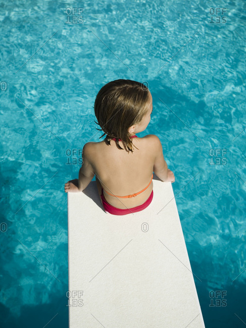 Little girl sitting on edge of diving board