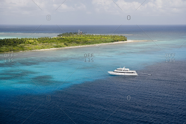 Aerial view of a large liveaboard dive boat off an island in Belize