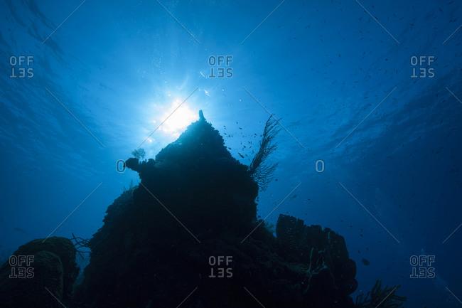 Silhouette of undersea mount with sunburst behind