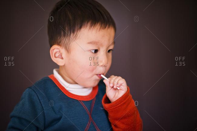 Little boy eating lollipop