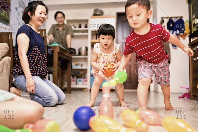 Children playing plastic bowling at home
