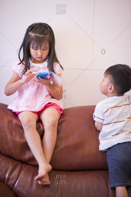 Two children playing on a couch