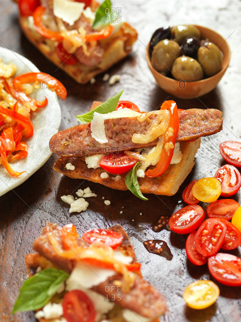 Italian bruschetta with bell pepper, cherry tomato, basil and sausage, garnish with parmesan cheese, served with fresh olives