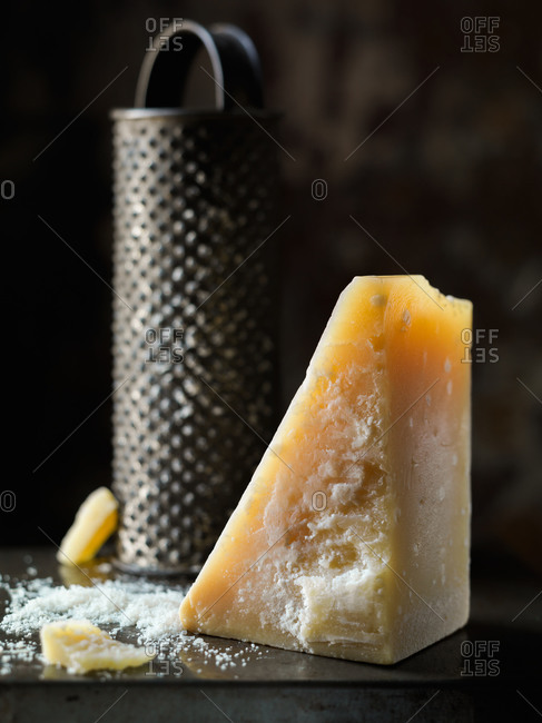 Block of parmesan cheese with vintage grater