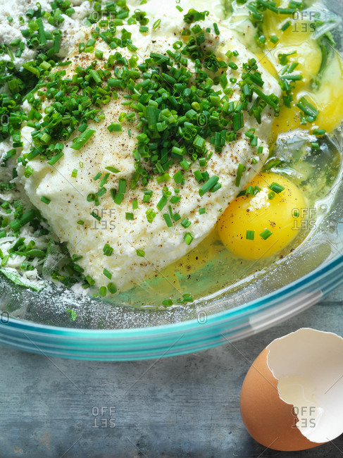 Overhead view of ricotta, chives and egg in a glass bowl