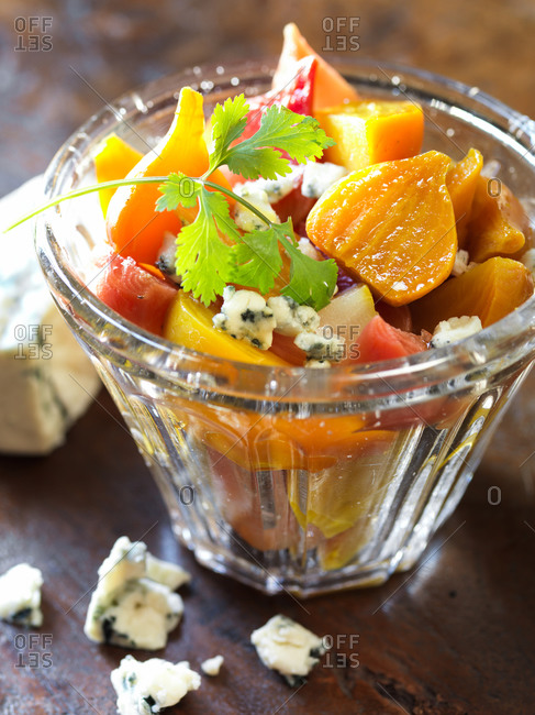Roasted multicolored beets in a serving bowl with blue cheese and cilantro garnish