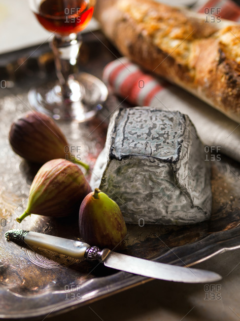 Valencay Cheese with figs, baguette and wine served on antique tray