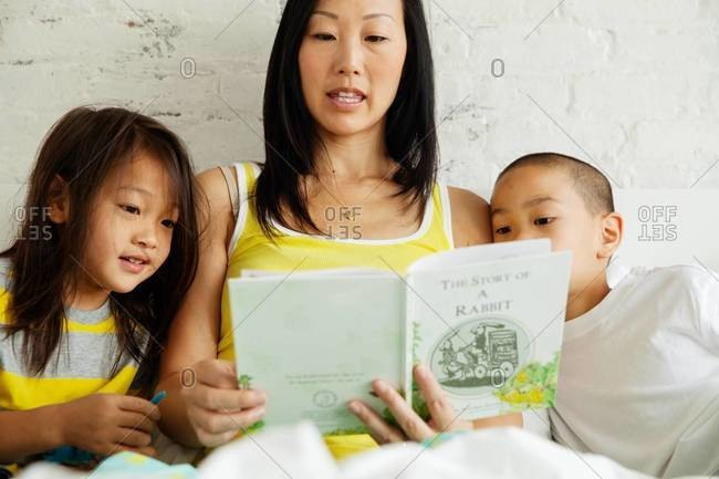 Mother reading bedtime story for her children