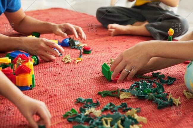 Family playing with toy soldiers and blocks on the floor