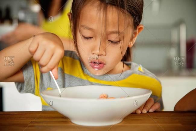 Little girl eating cereal for breakfast