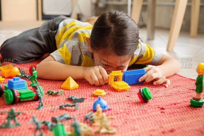 Little girl playing with toy soldiers and blocks on the floor