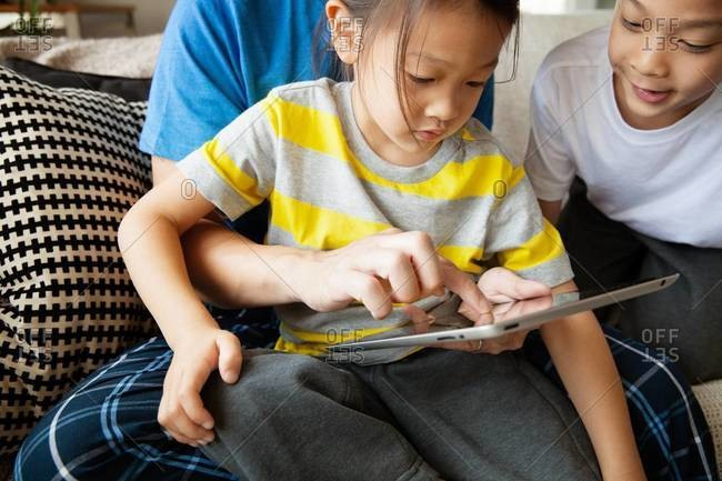 Father and children playing with tablet computer