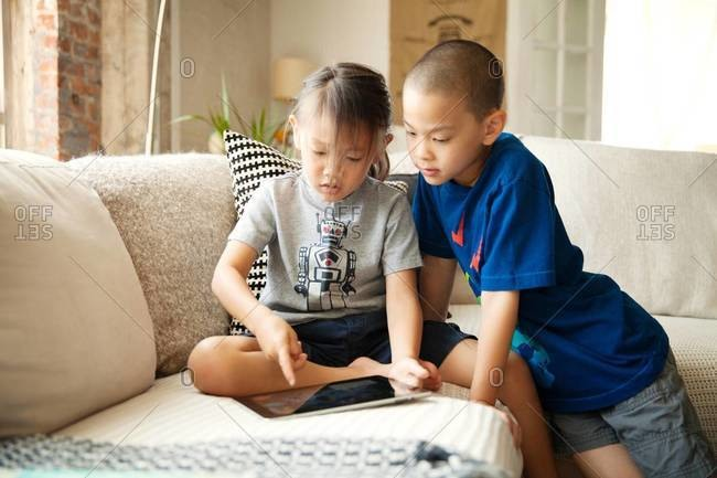 Siblings playing with tablet computer