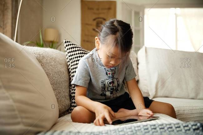 Little girl playing with tablet computer