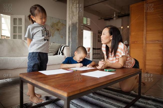 Mother and children drawing with crayons