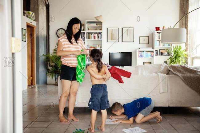 Mother dressing up her daughter while her son is drawing on the floor