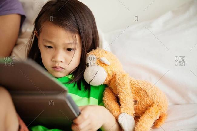 Girl reading a tablet in the bed
