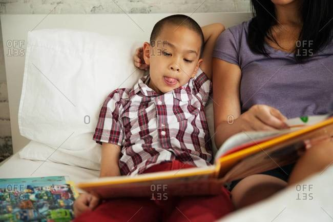 Boy reading a book in the bed with his mother
