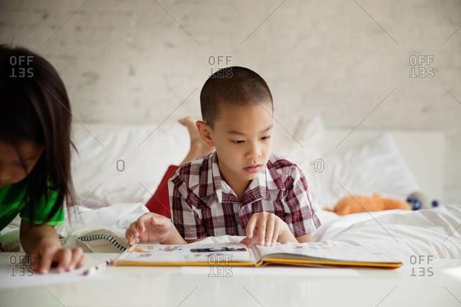 Boy reading a book in the bed