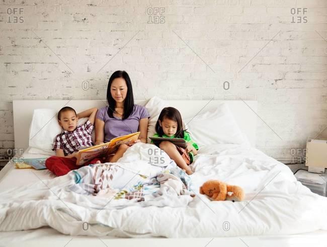 Mother reading bedtime story for her children