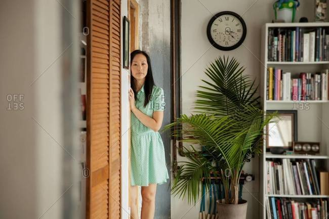 Portrait of woman leaning on doorway
