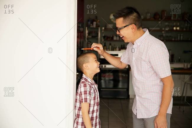 Father measuring his son's height