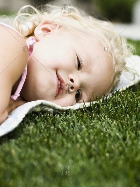 Little girl lying on a blanket on the grass.
