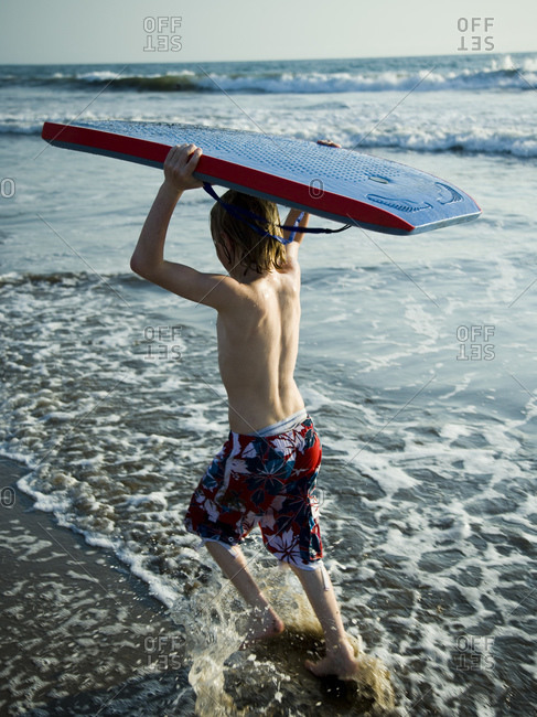 Boy running at the beach with a boogie board.