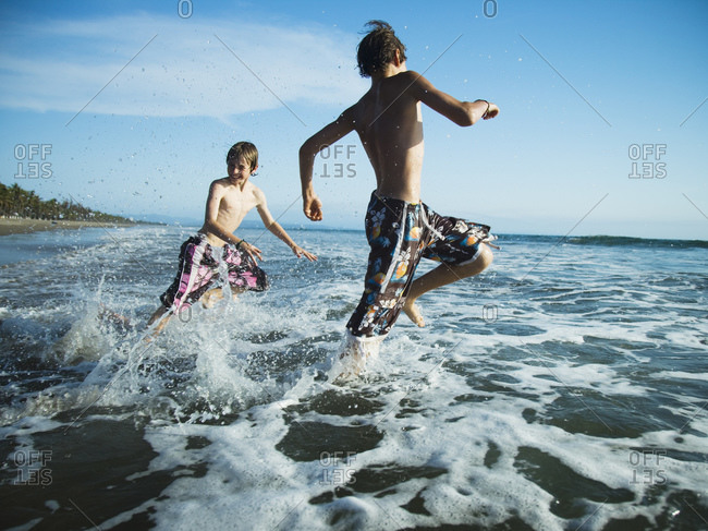 Two boys on beach running in surf