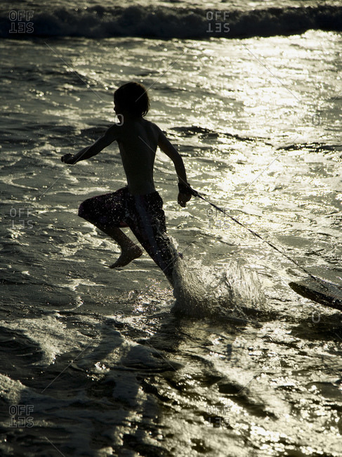 Boy running on beach with boogie board