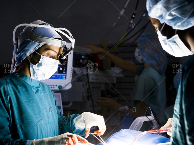 Female nurse and surgeon in scrubs during surgery