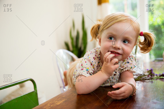 A little girl smiles while standing at a table