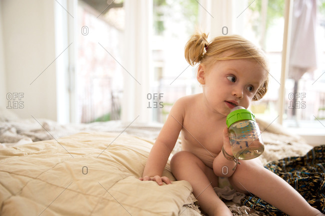 Portrait of little girl sitting on bed at home