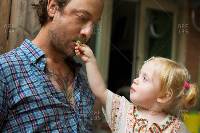 A little girl feeds her father