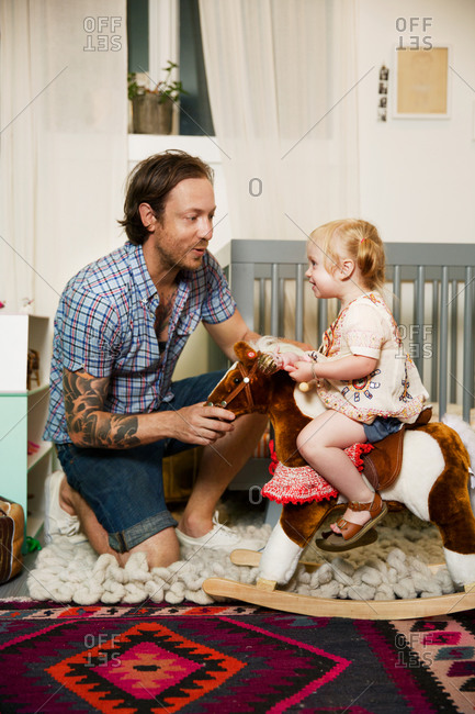 A father and daughter play together in the child's room